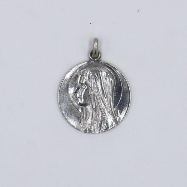 Medalla de la Virgen de Lourdes por un lado y por el otro la aparición en la gruta con Santa Bernardita